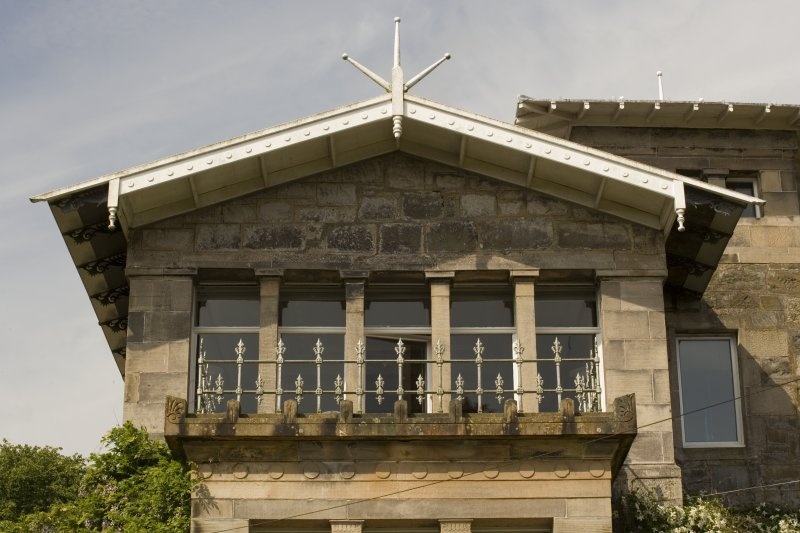 Detail of first floor window, balcony and finial above on E facade