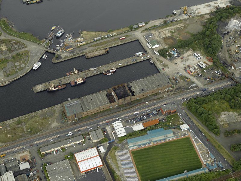 Oblique aerial view centred on the burnt out sugar warehouse and the docks, taken from the SW.