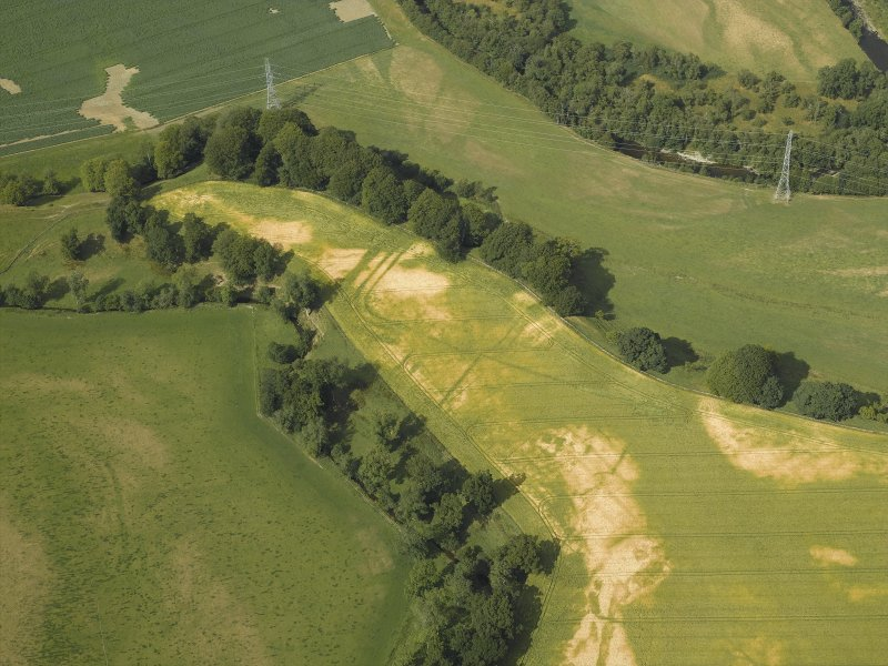 Oblique aerial view centred on the cropmarks of the Roman fortlet, Roman temporary camp and settlement, taken from the S.