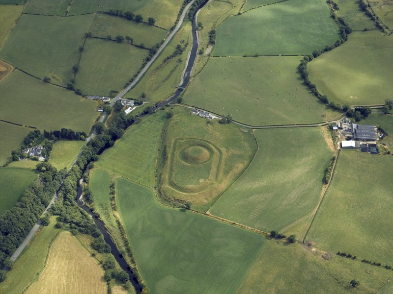 Oblique aerial view centred on the remains of the motte and bailey castle, taken from the NW.