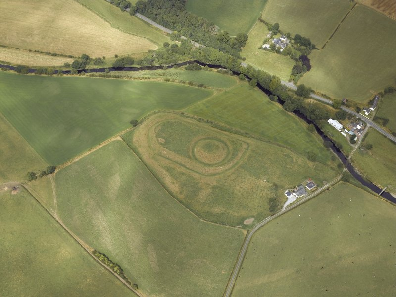 Oblique aerial view centred on the remains of the motte and bailey castle, taken from the SW.