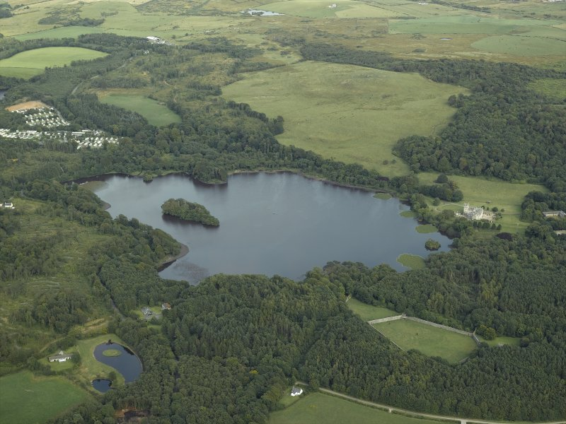 General oblique aerial view centred on Lochnaw Loch and towerhouse, with the towerhouse and country house adjacent, taken from the NW.