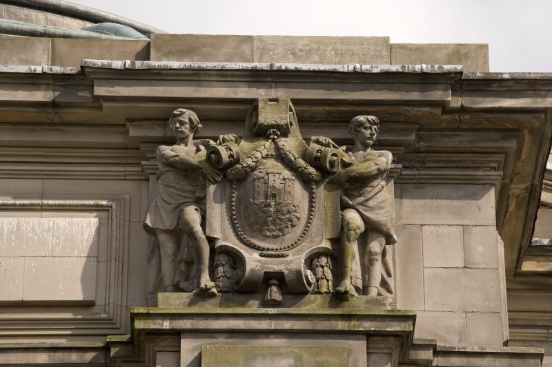 Detail of statues above entrance on NW face, youths supporting the City of Edinburgh Arms