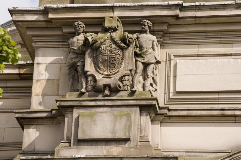 Detail of statues above entrance on NW face, youths supporting Royal Arms