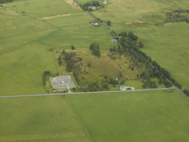 Oblique aerial view centred on the remains of the Roman temporary camp with the cottage and tollhouse adjacent, taken from the SW.