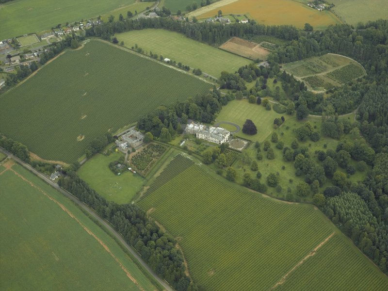 Oblique aerial view centred on the country house, castle, stables, lodge and walled garden, taken from the WSW.