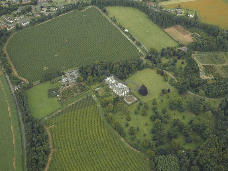 Oblique aerial view centred on the country house, castle, stables and lodge, taken from the SW.