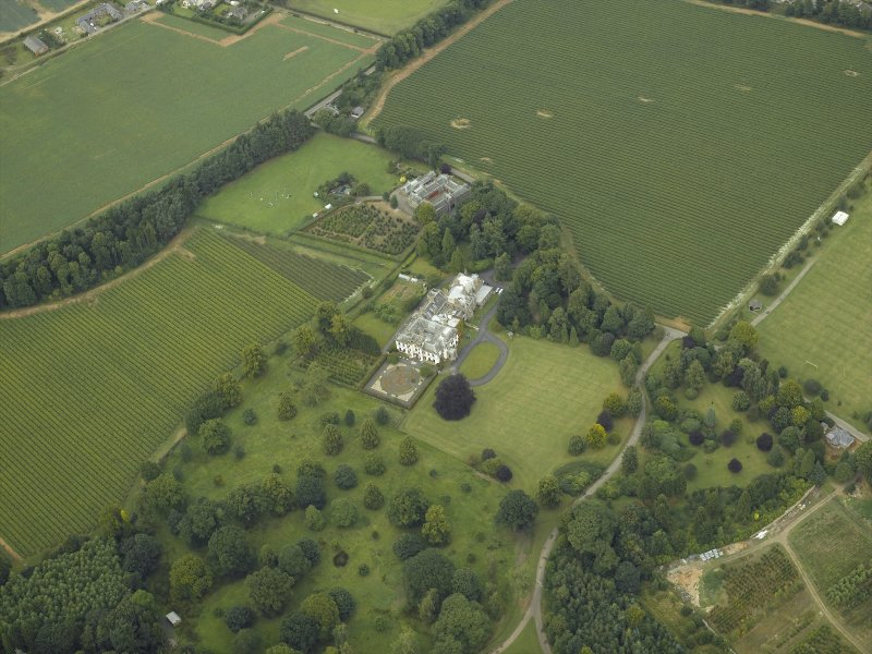Oblique aerial view centred on the country house, castle, stables and lodge, taken from the S.