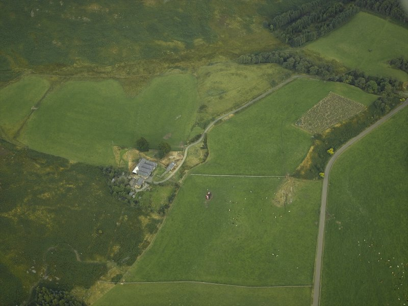 Oblique aerial view centred on the remains of the stone circle and the farmhouse and farmsteading, taken from the W.
