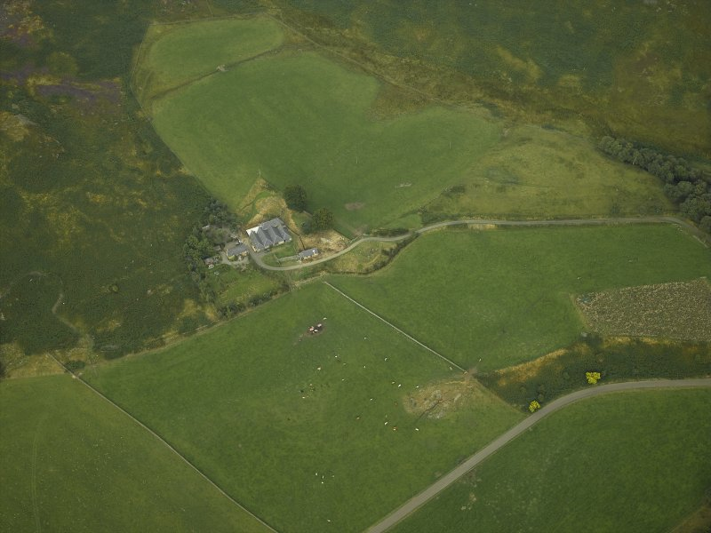 Oblique aerial view centred on the remains of the stone circle and the farmhouse and farmsteading, taken from the SW.