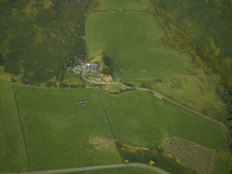 Oblique aerial view centred on the remains of the stone circle and the farmhouse and farmsteading, taken from the SSW.