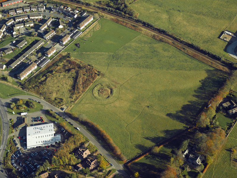 Oblique aerial view centred on the remains of the henge and stone circle, taken from the SW.