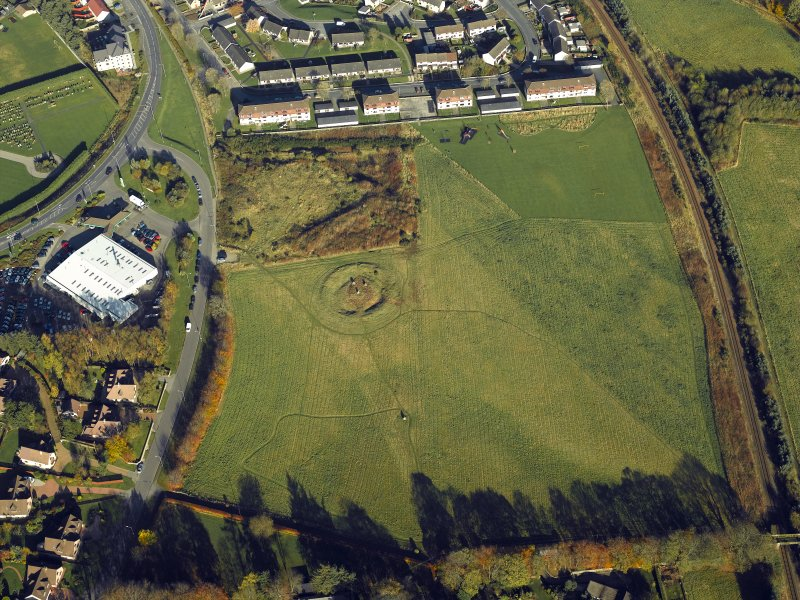 Oblique aerial view centred on the remains of the henge and stone circle, taken from the SSW.