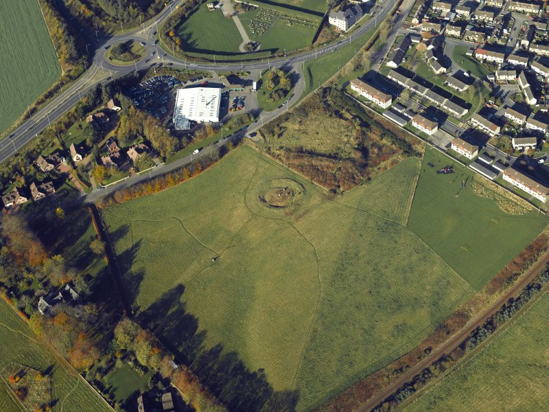 Oblique aerial view centred on the remains of the henge and stone circle, taken from the SE.