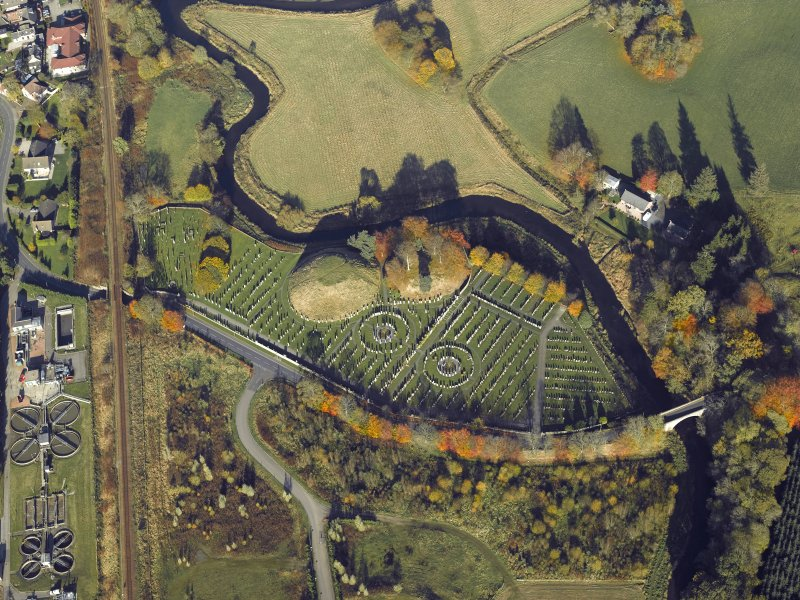 Oblique aerial view centred on the remains of the motte and bailey castle and the cemetery, taken from the SSE.