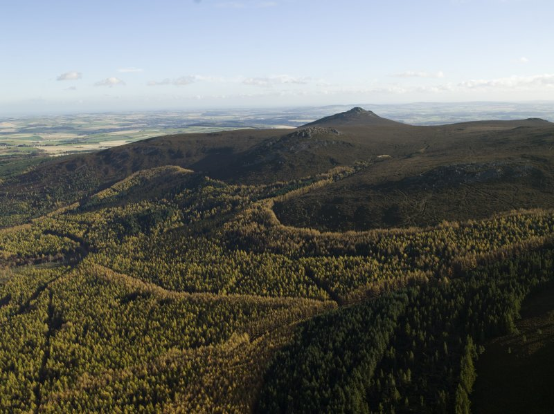 Oblique aerial view centred on the remains of the fort at Bennachie, taken from the NW.