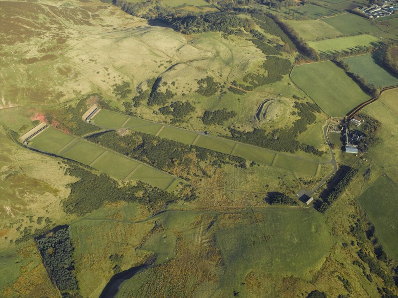 General oblique aerial view centred on the rifle ranges with the farmhouse and farmsteading and remains of the rig, fort, cultivation terraces and palisaded settlement adjacent, taken from the SW.