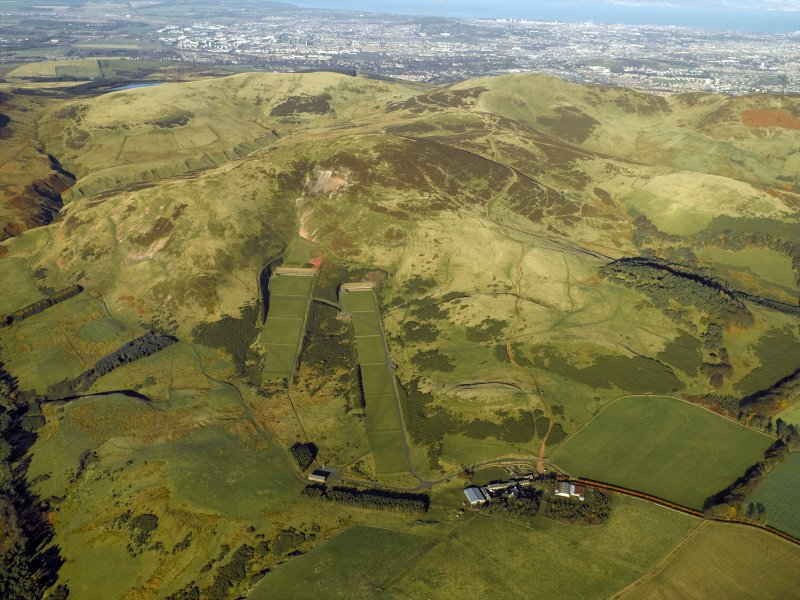 General oblique aerial view centred on the rifle ranges, farmhouse and farmsteading and the remains of the rig, fort, cultivation terraces and palisaded settlement, taken from the SE.