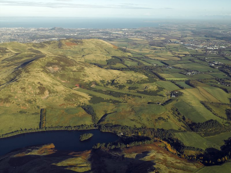 General oblique aerial view centred on the rifle ranges, farmhouse and farmsteading and the remains of the rig, fort, cultivation terraces and palisaded settlement, taken from the SW.
