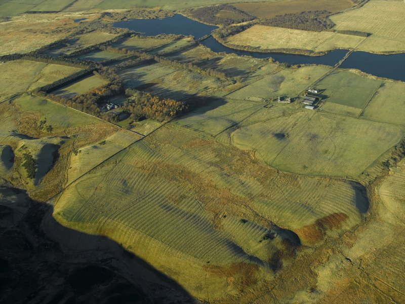 General oblique aerial view centred on the remains of the rig with the fortified house and remains of the rig, enclosures and farmstead adjacent, taken from the NW.