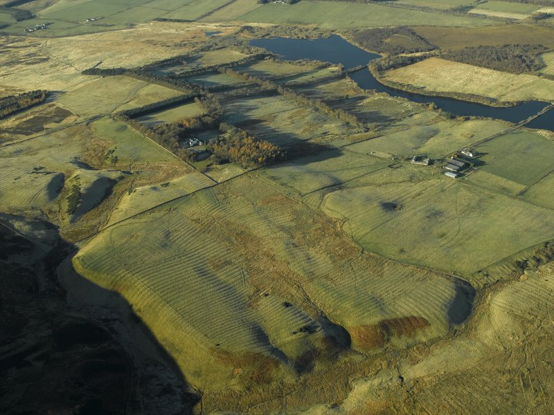 General oblique aerial view centred on the remains of the rig with the fortified house and remains of the rig, enclosures and farmstead adjacent, taken from the WNW.