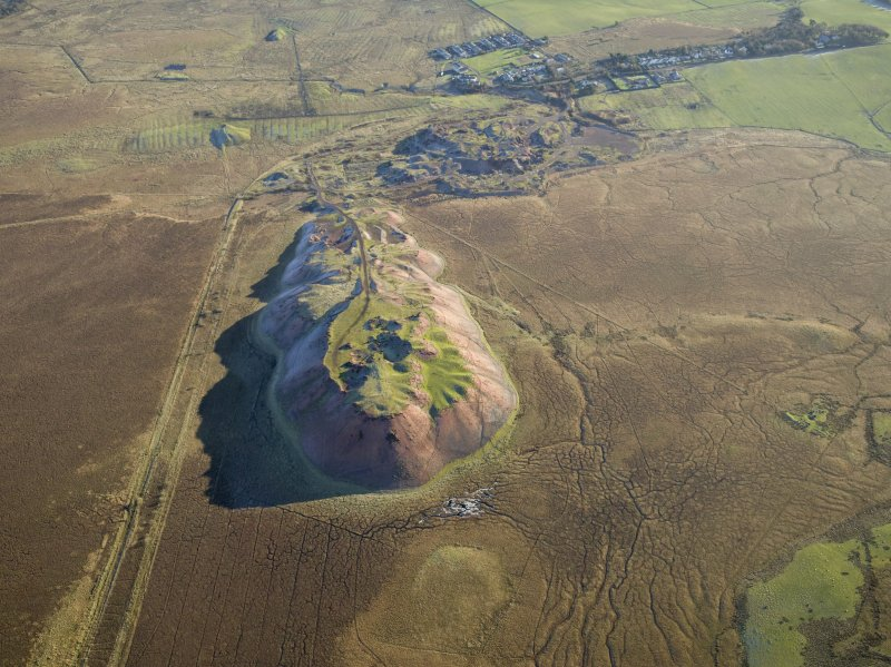 Oblique aerial view centred on the shale-oil works, remains of the shale bings and shale-oil mines with the village and remains of the rig adjacent, taken from the WNW.