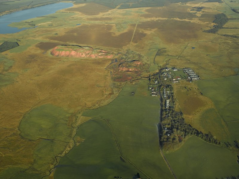 General oblique aerial view centred on the shale-oil works, remains of the shale bings, shale-oil mines, village and remains of the rig, taken from the SSW.