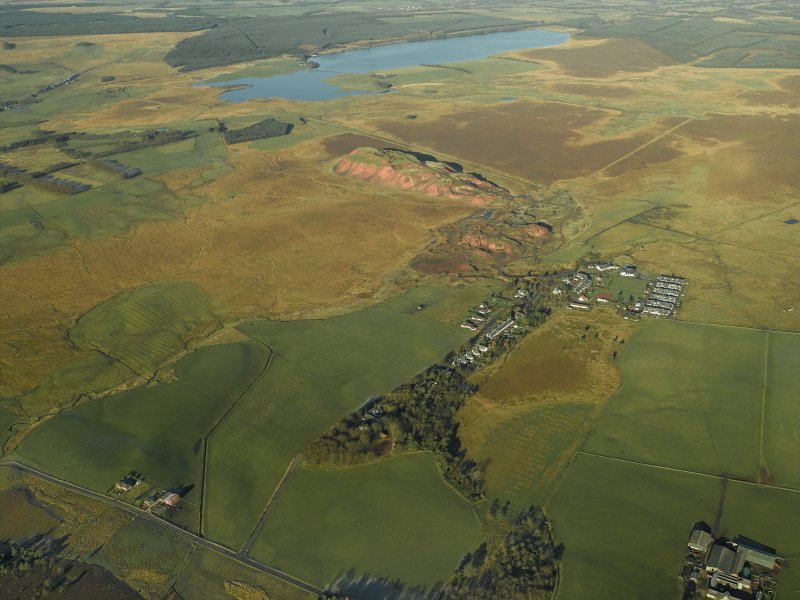 General oblique aerial view centred on the shale-oil works, remains of the shale bings, shale-oil mines, village and remains of the rig, taken from the SE.