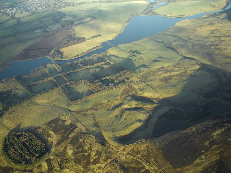 General oblique aerial view centred on the remains of the rig and field systems with the fortified house and reservoir adjacent, taken from the SW.