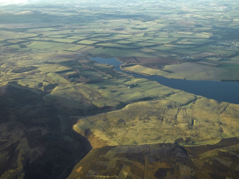 General oblique aerial view centred on the remains of the rig and field systems with the fortified house and reservoir in the distance, taken from the ESE.