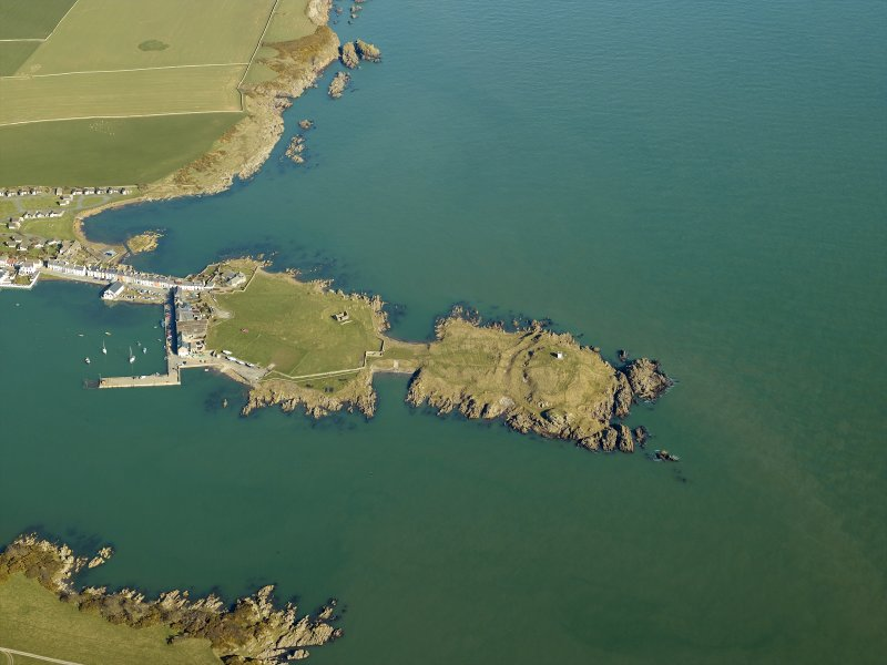 Oblique aerial view centred on the remains of the promontory fort and the chapel, taken from the SW.