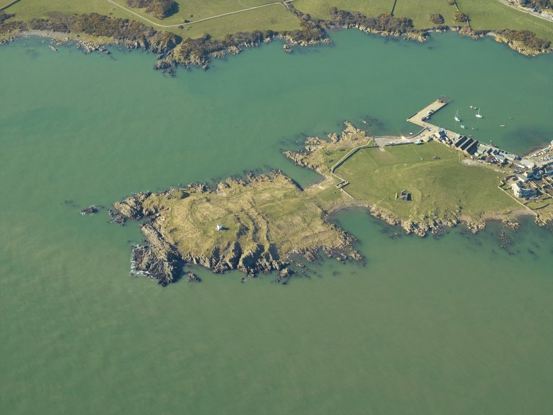 Oblique aerial view centred on the remains of the promontory fort and the chapel, taken from the ENE.