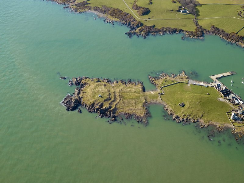 Oblique aerial view centred on the remains of the promontory fort and the chapel, taken from the NE.