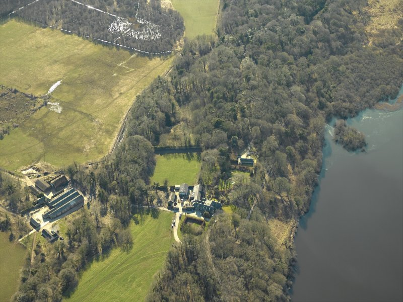 Oblique aerial view centred on the remains of the castle and crannog with the cottage and offices adjacent, taken from the NNE.