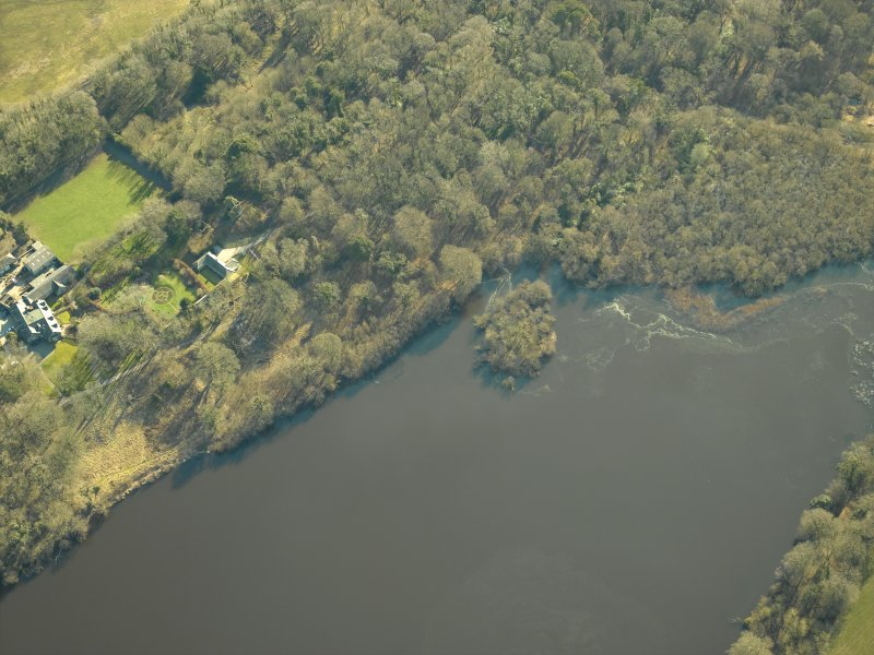 Oblique aerial view centred on the remains of the crannog with the remains of the castle, and the cottage and offices adjacent, taken from the NW.