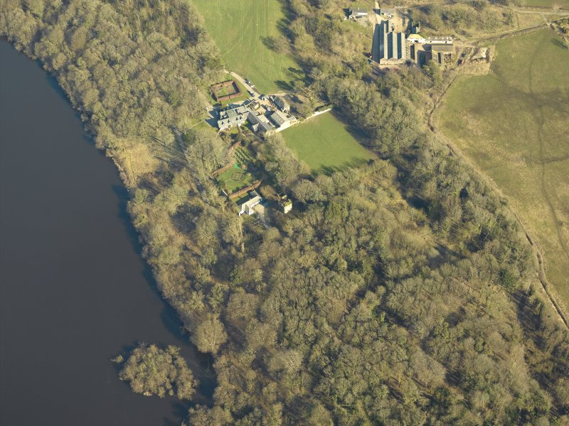 Oblique aerial view centred on the remains of the castle and crannog with the cottage and offices adjacent, taken from the SW.
