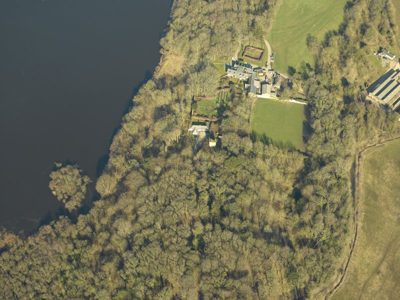 Oblique aerial view centred on the remains of the castle and crannog with the cottage and offices adjacent, taken from the SSE.