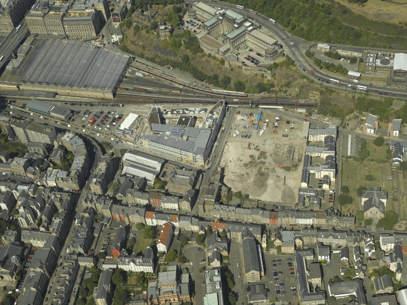 Oblique aerial view centred on the railway goods station and the construction of the car park with the offices adjacent, taken from the SE.