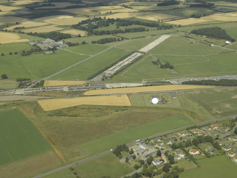 General oblique aerial view centred on the radio station and airfield with the aircraft hangars in the distance, taken from the SSE.