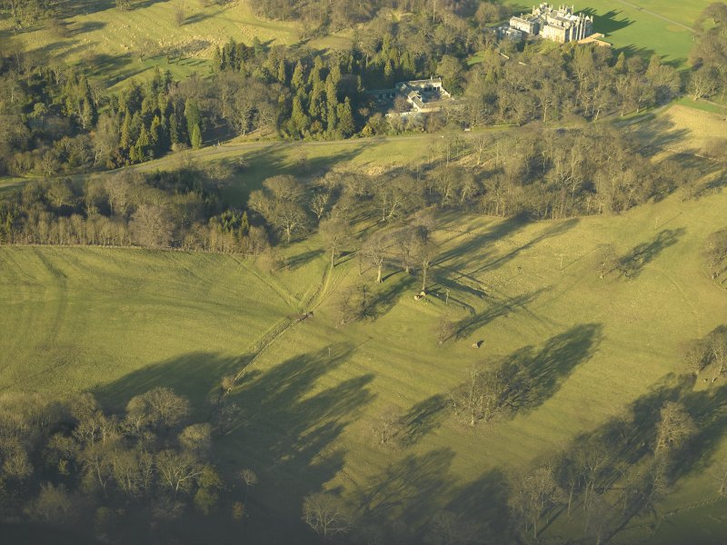 Oblique aerial view centred on the remains of the rig with the stables and country house adjacent, taken from the SSE.