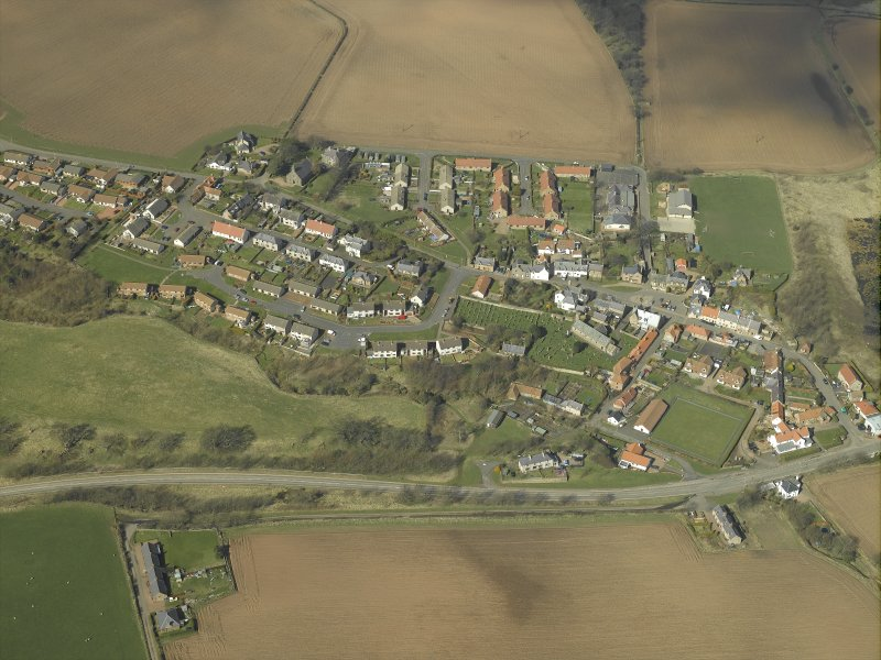 General oblique aerial view of the village, centred on the church, burial-ground and churchyard with the hotel and stable adjacent, taken from the SE.