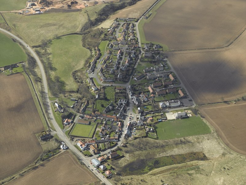 General oblique aerial view of the village, centred on the church, burial-ground and churchyard with the hotel and stable adjacent, taken from the NE.