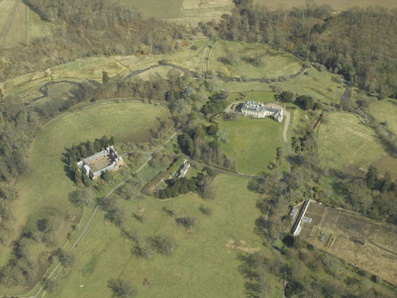 General oblique aerial view centred on the country house, stables, glasshouse and walled garden, taken from the SW.