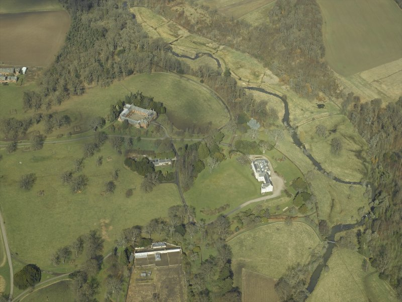 General oblique aerial view centred on the country house, stables and glasshouse, taken from the S.