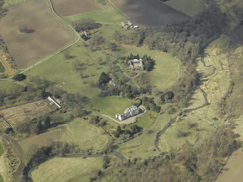 General oblique aerial view centred on the country house, stables, glasshouse and walled garden, taken from the E.