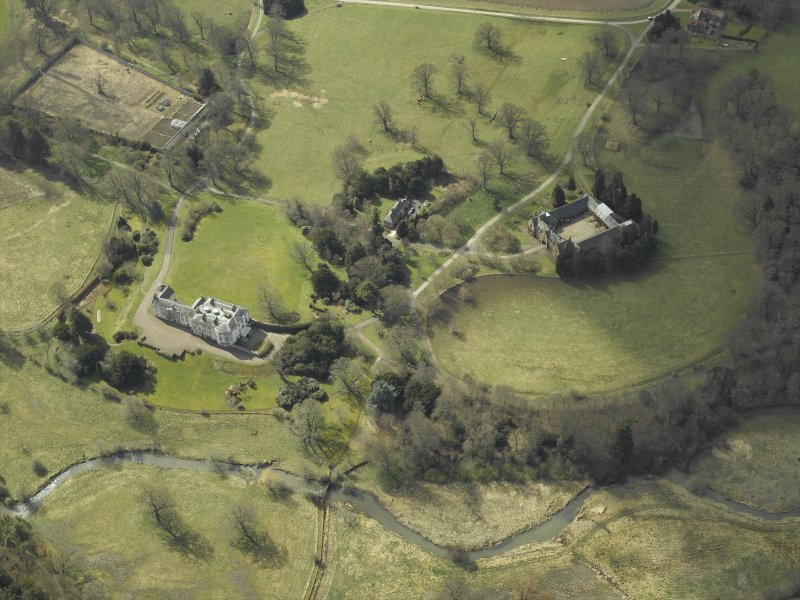 General oblique aerial view centred on the country house, stables, glasshouse and walled garden, taken from the NE.