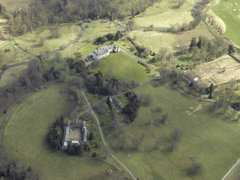 General oblique aerial view centred on the country house, stables, glasshouse and walled garden, taken from the W.