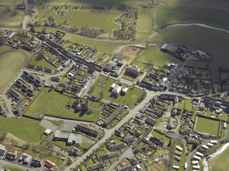 General oblique aerial view of the village centred on the county building, court house and town hall with the church, churchyard, burial-ground and hotel adjacent, taken from the NW.