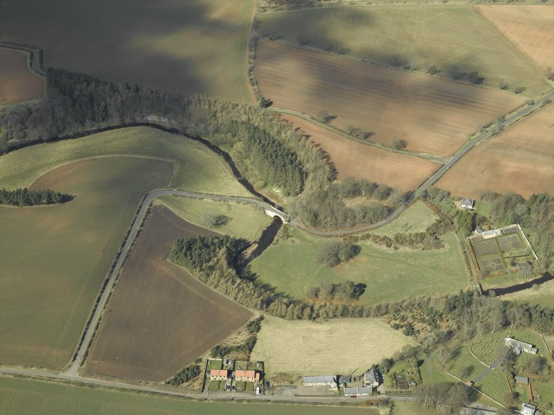 Oblique aerial view centred on the road bridge with the walled garden, bothy, church, burial-ground and churchyard adjacent, taken from the SE.