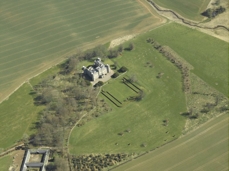 Oblique aerial view centred on the country house, stable block and landscaped gardens, taken from the W.